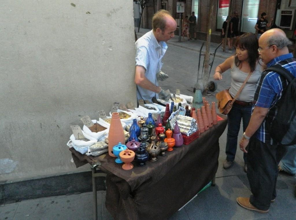 """I """"vendedores de humo"""" cercano di invogliare la clientela bruciando parte del loro prodotto."""